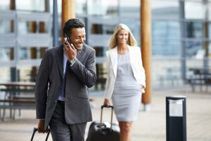Business man walking with luggage outdoors using cell phone with woman in background